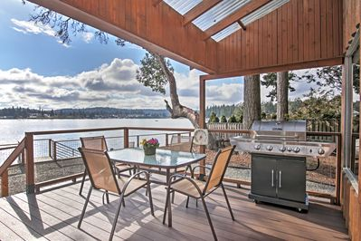 Gather outside on the covered deck, overlooking the water.