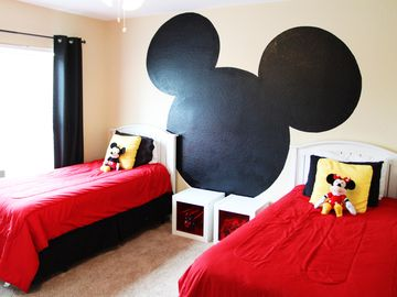 Mickey twin room with toys in nightstands and large chest of drawers.