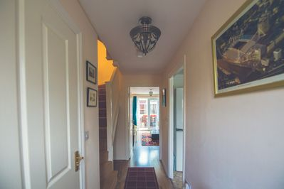 Hallway with toilet to left & kitchen to the right, understairs coat rack