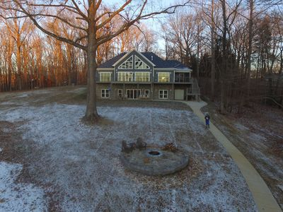 Large back lawn and fire pit; paved sidewalk to dock