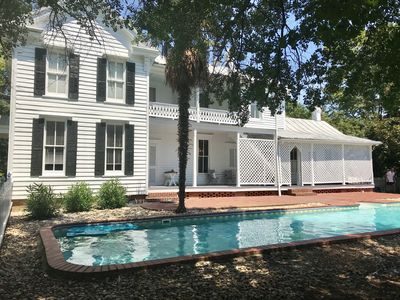 Lovely home with inviting pool.  A view from beneath the live oak tree.