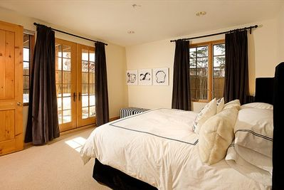 Elegant master bedroom with lovely linens and private patio.