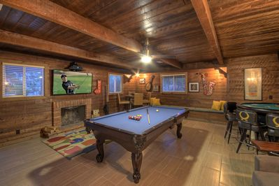 Rustic game room has pool and card tables, a TV, a wood burning fireplace and queen bed in the corner