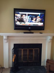 Flat Screen TV above the wood burning fireplace.
