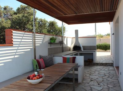 Shaded outdoor dining area and kitchen with pizza oven