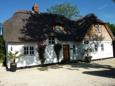 Photo for Beautifully Appointed Riverside Thatched Cottage. Town Centre, Yet Secluded