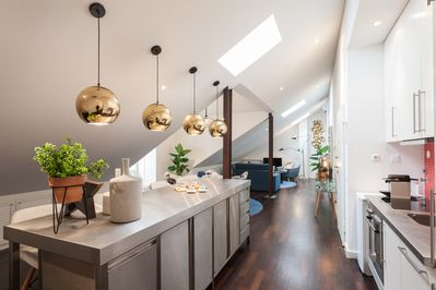 Full perspective of the loft's open space, with kitchen, dining and living areas