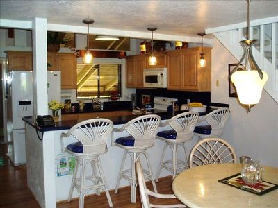 Fully furnished kitchen, snack bar, and dining room