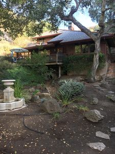 Two story house, deck, an acre of landscaped grounds, fountain, seasonal creek