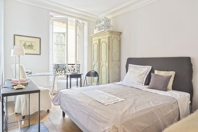 The spacious bedroom include a glass desk with comfortable chair and an armoir