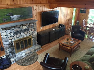 Comfortable, clean and modern living room with fireplace, large screen TV.