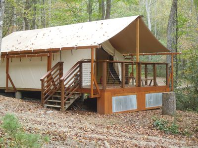 Luxury tent has 4 bunk beds, night stands, table, & book case.