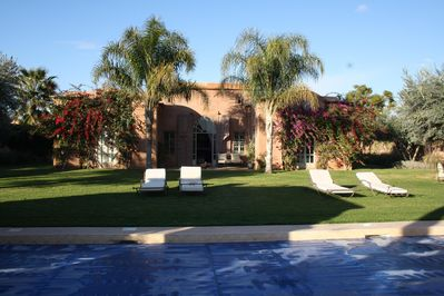 Front of villa with magnificent pool and garden