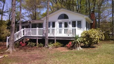 View of the deck and sunroom from the lakefront yard.