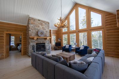 Large living room with wood fireplace and panoramic views on nature.