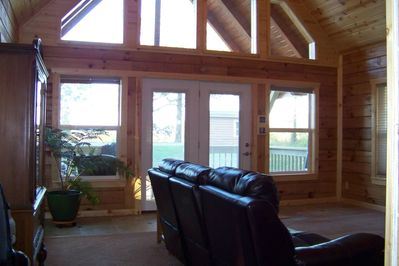 living room with window wall, looking out to the front porch