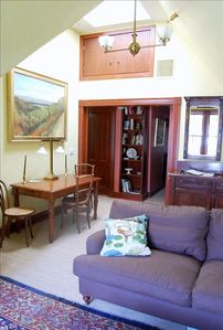 The airy sitting room has tall windows, a cathedral ceiling & a skylight.