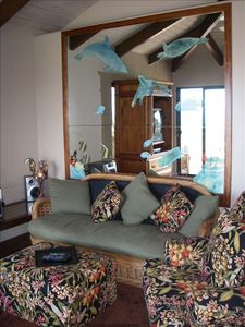 Livingroom sofa and designer mirror, beautiful stained-glass parrot lamp