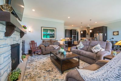 living room has 3 motorized reclining easy chairs around the fireplace.