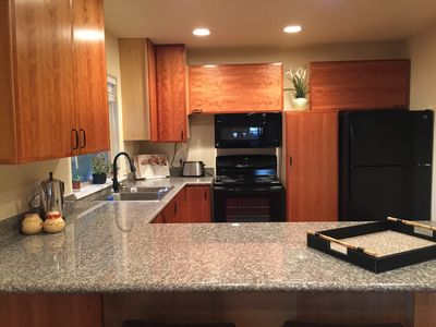 fully equipped kitchen with peninsula counter and stools