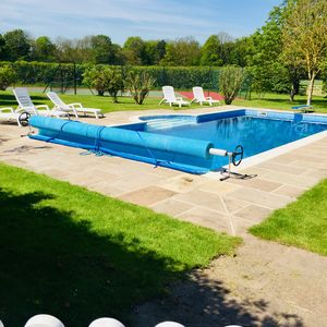 Heated outdoor pool with pool house and tennis court alongside