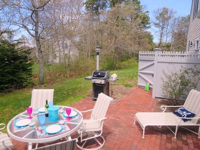 View of the patio with a gas grill, outdoor shower, and yard - 30 Cockle Cove Road Chatham Cape Cod New England Vacation Rentals