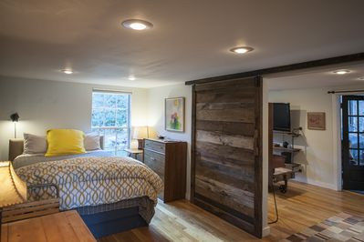 Beautifully decorated bedroom with new queen bed, sliding barn door to living rm