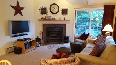 Living room with flat screen and wood burning fire place.