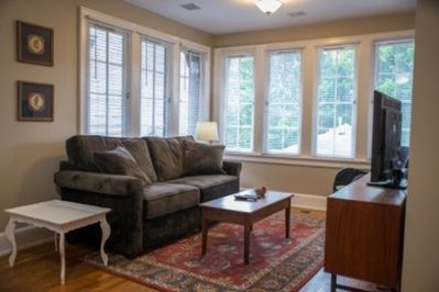 Living room with bank of windows, some may be opened.