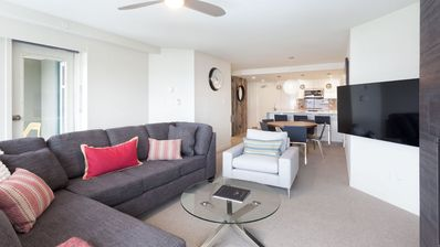 Spacious and bright living area with large screen TV.