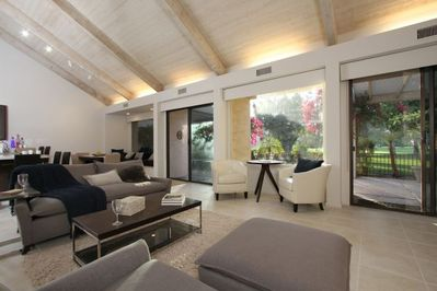 Contemporary living room showing cathedral ceiling to patio and golf fairway
