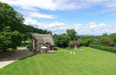 Photo for On the slopes of Bredon Hill in a truly idyllic location, a picture-book thatched cottage.