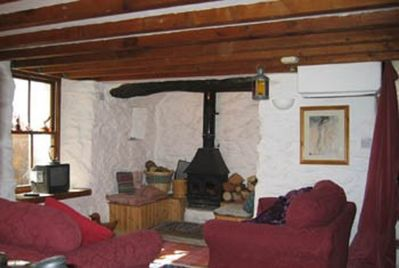 Farmhouse living room with woodstove+seating in original inglenook...