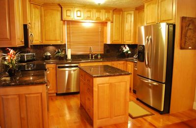 Kitchen with Granite Counter tops, Stainless Steel Appliances and Hardwood Floor