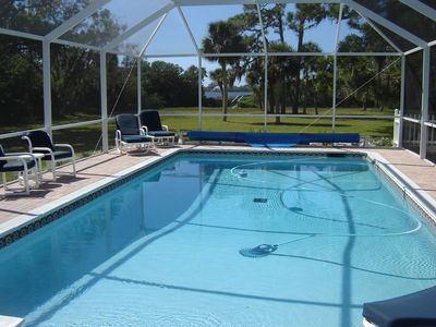 Relax in the sunshine by the pool while overlooking the backyard and the bay
