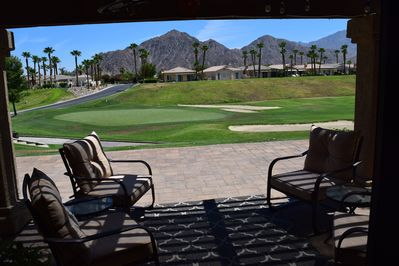Back patio view of the green and mountain back drop