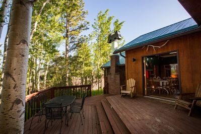 Large outside deck looking out to grove of aspen trees. Dining rm to right.