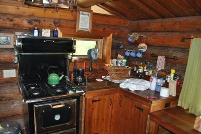 Repro gas range w/elect oven, copper sink w/reverse osmosis water. Bit cluttered