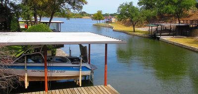 Secluded lake house w/ 2-story boat dock and many trees.