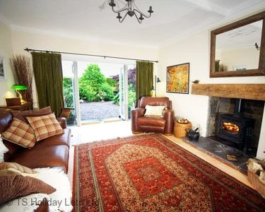 Strathview Cottage - lounge showing sofas, fire & doors to garden