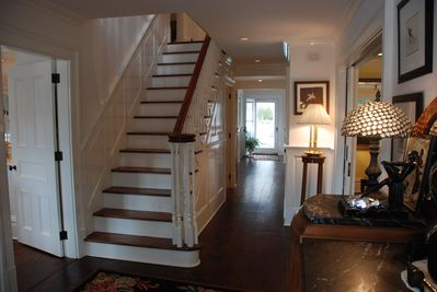 Central hall w/ paneled staircase & pocket doors to Living Room; view to 2 f/pls