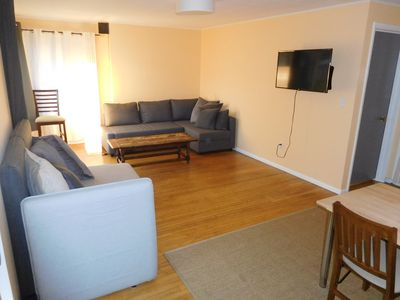 Living room with sofa bed, couch, Roku TV, dining table.