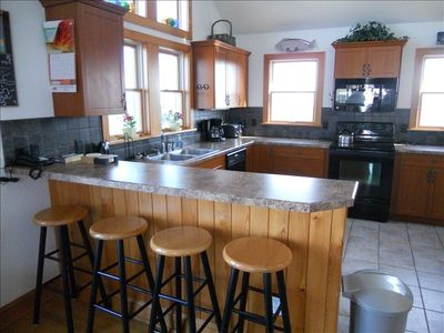 Great open Kitchen with bar seating and four bar stools opens into Dining Room