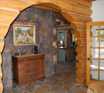 View from Foyer at rock wall forming fireplaces with lighted built-in niches.