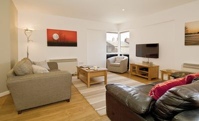 """Lounge with comfortable sofas, balcony and 40"""" Smart TV with wireless keyboard"""