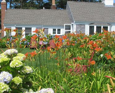 Garden flowers and cottage in summer. BR with king bed to the left.  Great room windows far right.