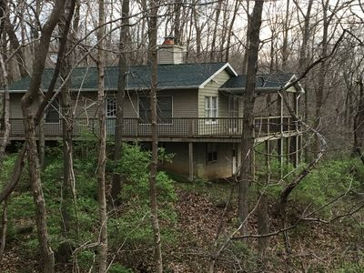 1728 sf house with partially covered deck on a heavily wooded property