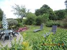 68/5000 Flowery garden in front of the house with table, deck chairs and umbrella