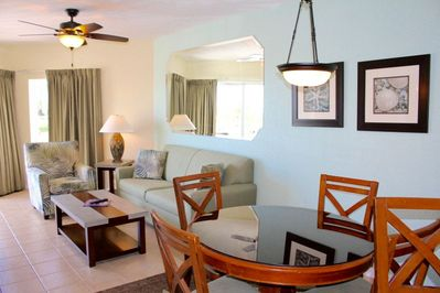 Nicely decorated living room and dining area with a table for 4 guests