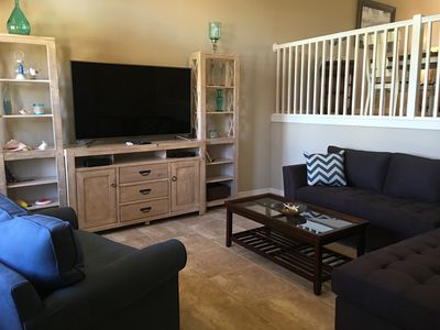 "Comfortable family room equipped with a 65"" TV to enjoy a movie"